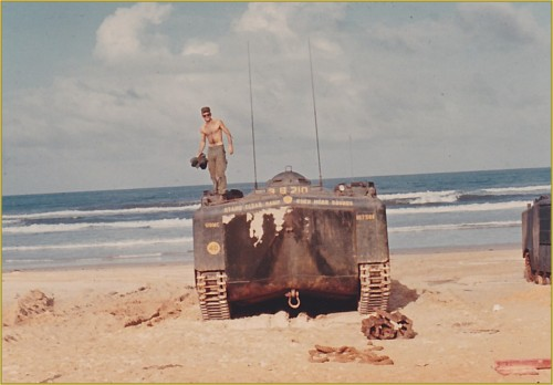 Cpl Joe McNeil standing on an Amtrac on the beach